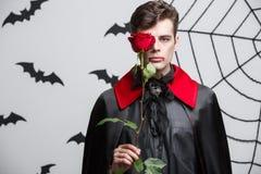 Concept de Halloween de vampire - le portrait du vampire caucasien beau tenant beau rouge s'est levé Photos stock
