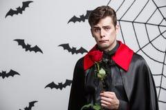 Concept de Halloween de vampire - le portrait du vampire caucasien beau tenant beau rouge s'est levé Photo stock
