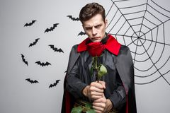 Concept de Halloween de vampire - le portrait du vampire caucasien beau tenant beau rouge s'est levé Images libres de droits