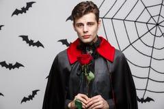 Concept de Halloween de vampire - le portrait du vampire caucasien beau tenant beau rouge s'est levé Image stock
