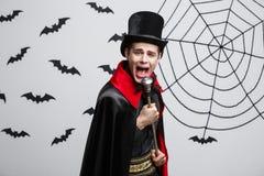 Concept de Halloween de vampire - portrait du vampire caucasien beau dans le costume noir et rouge de Halloween chantant avec le  Photos libres de droits