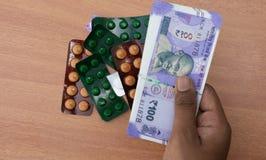 Concept de handen die van de persoon Pillen of tabletten met Indische munt kopen stock afbeeldingen
