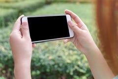 Concept de holdingstelefoon van de Vrouwenhand en het letten op video op slim Stock Afbeeldingen