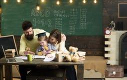 Concept de Homeschooling Les parents enseigne le fils, tableau sur le fond Garçon écoutant la maman et le papa avec l'attention photos libres de droits