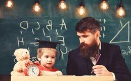Concept de Hometask Enfant enthousiaste ?tudiant avec le professeur Professeur dans le tenue de soir?e et l'?l?ve dans la taloche images stock