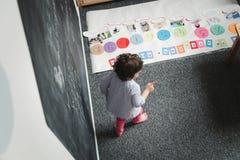 Concept de jardin d'enfants Dessin préscolaire heureux de fille sur le tableau noir et l'amusement de avoir image stock