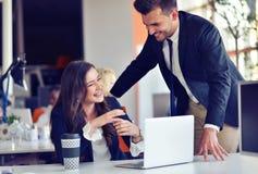 Concept de jeune entreprise avec de jeunes couples multi-ethniques dans le bureau moderne travaillant sur l'ordinateur portable Photo stock
