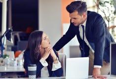 Concept de jeune entreprise avec de jeunes couples multi-ethniques dans le bureau moderne travaillant sur l'ordinateur portable Images stock