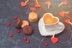 Concept de jour de valentines avec la tasse de café de forme de coeur et macarons au-dessus de tableau noir Photos stock