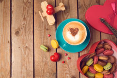 Concept de jour de valentines avec les macarons, la tasse de café et l'avion de jouet au-dessus du fond en bois Vue supérieure Image stock