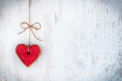Concept de jour de Valentines Biscuit en forme de coeur attaché avec l'arc de chanvre au-dessus du fond rustique en bois blanc image libre de droits