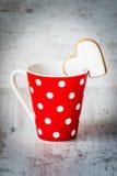 Concept de jour de Valentines La polka rouge de café a pointillé la tasse avec un biscuit fait maison en forme de coeur au-dessus Images libres de droits