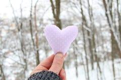 Concept de jour du ` s d'hiver, d'amour ou de Valentine Remettez tenir un coeur sur le fond de la forêt d'hiver Photo libre de droits