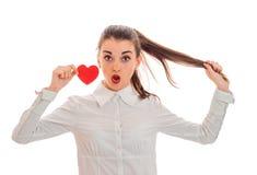 Concept de jour du ` s de Valentine Amour Fille étonnée par jeunes avec le coeur rouge d'isolement sur le fond blanc dans le stud Images libres de droits