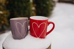 Concept de jour du ` s de Valentine avec des coeurs et des tasses au-dessus de nature Photographie stock