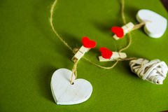 Concept de jour du ` s de Valentine Coeurs en bois blancs fixes avec des pinces à linge sur la corde sur le fond vert Images libres de droits