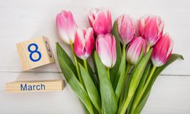Concept de jour du ` s de femmes Les tulipes roses et le 8 mars datent sur le fond blanc Photo stock