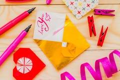 Concept de jour du ` s de Valentine coeurs d'origami et enveloppe d'or avec stationnaire sur le fond rustique en bois Photographie stock libre de droits