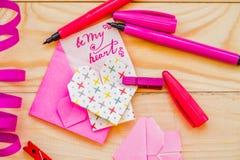 Concept de jour du ` s de Valentine coeurs d'origami et enveloppe rose avec stationnaire sur le fond rustique en bois Photo stock
