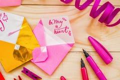 Concept de jour du ` s de Valentine coeurs et enveloppes d'origami avec stationnaire sur le fond rustique en bois Image libre de droits