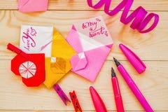 Concept de jour du ` s de Valentine coeurs et enveloppes d'origami avec stationnaire sur le fond rustique en bois Photographie stock libre de droits