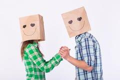 Concept de jour du ` s de Valentine - jeune ajouter d'amour aux sacs au-dessus des têtes sur le fond blanc Photo stock