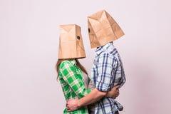 Concept de jour du ` s de Valentine - jeune ajouter d'amour aux sacs au-dessus des têtes sur le fond blanc Image libre de droits