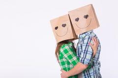 Concept de jour du ` s de Valentine - jeune ajouter d'amour aux sacs au-dessus des têtes sur le fond blanc Image stock