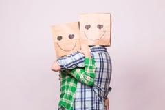 Concept de jour du ` s de Valentine - jeune ajouter d'amour aux sacs au-dessus des têtes sur le fond blanc Photographie stock