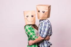 Concept de jour du ` s de Valentine - jeune ajouter d'amour aux sacs au-dessus des têtes sur le fond blanc Photographie stock libre de droits