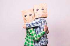 Concept de jour du ` s de Valentine - jeune ajouter d'amour aux sacs au-dessus des têtes sur le fond blanc Photos libres de droits