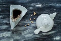 Concept de jour du ` s de Valentine, théière blanche avec la tasse triangulaire et coeur en bois sur le fond bleu, lumière nature Photographie stock libre de droits