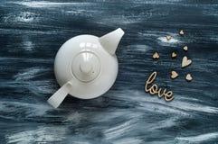 Concept de jour du ` s de Valentine, théière blanche et coeurs en bois sur un fond bleu, lumière naturelle, l'espace pour le text Image stock