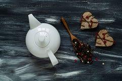 Concept de jour du ` s de Valentine, théière blanche et deux coeurs en bois sur le fond bleu et blanc, lumière naturelle, vue sup Images libres de droits