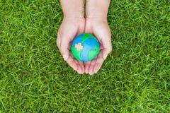 Concept de jour de terre du monde Main de femme tenant le globe fait main Photographie stock libre de droits