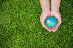 Concept de jour de terre du monde Main de femme tenant le globe fait main Photographie stock