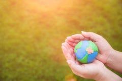 Concept de jour de terre du monde Main de femme tenant le globe fait main Images stock