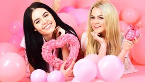 Concept de jour de Valentines Les filles s'étendent près des ballons, jouets de coeur de prises, fond rose Blonde et brune sur le Photos libres de droits