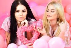 Concept de jour de Valentines Les filles s'étendent près des ballons, jouets de coeur de prises, fond rose Soeurs, amies dans des Images libres de droits