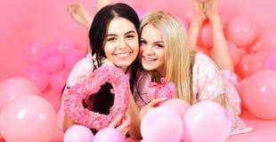 Concept de jour de Valentines Soeurs, amies dans des pyjamas à la partie de pyjamas Blonde et brune sur rêver de sourire de visag Images libres de droits