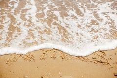 Concept de Joyeux Noël, bonnes fêtes Texte de Noël sur la plage sablonneuse photographie stock