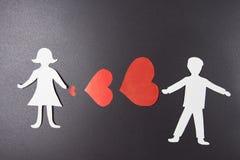 Concept de l'amour Coeurs rouges entre l'homme et la femme du papier sur le fond noir Image stock