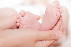 Concept de l'amour et de la famille mains de pied de mère et de bébé Images stock