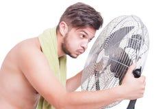 Concept de la chaleur d'été avec l'homme nu tenant le refroidisseur de soufflement Photos stock