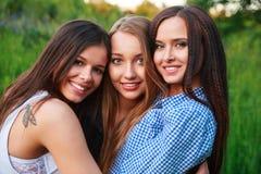 Concept de la Communauté de bonheur d'amitié d'amies Trois amis de sourire étreignant dehors dans la nature Images stock