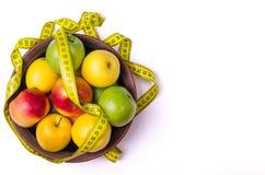Concept de la consommation saine, pommes fraîches dans un plat et mesure Photographie stock libre de droits