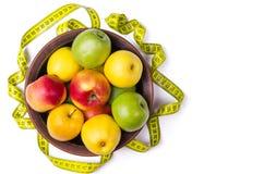 Concept de la consommation saine, pommes fraîches dans un plat et mesure Image stock