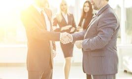 Concept de la coopération - poignée de main des associés sur le fond des employés dans le bureau Images stock