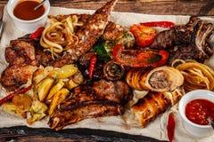 Concept de la cuisine géorgienne Grand panneau de viande avec le shashlik, la viande rôtie, les pommes frites, l'agneau de rôti e image stock