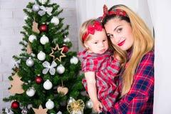 Concept de la famille de Noël et - femme avec la fille et décorée Images stock